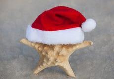 Sulla spiaggia, la sabbia è una stella marina che porta un cappello di Santa Claus Celebrazione il nuovo anno e del Natale nel ma Immagini Stock