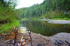 Sulla sponda del fiume con una cottura del fuoco Fotografie Stock Libere da Diritti