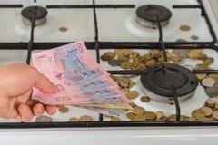 Sulla stufa di gas le monete sono sparse e una mano con una banconota ucraina vale 200 hryvnias fotografia stock libera da diritti