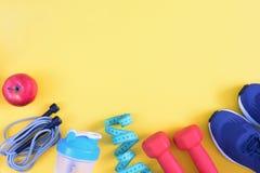 Sulla superficie gialla sono le teste di legno rosse, le scarpe da tennis, una bottiglia e una mela Il posto superiore per un'isc immagini stock