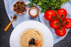 Sulla tavola è la pasta con le olive e gamberetti, ciliegia, prezzemolo, una miscela dei peperoni e un sale-vaso Fotografia Stock
