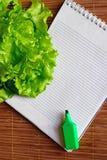 Sulla tavola è un taccuino, un indicatore e le foglie fresche della lattuga immagine stock