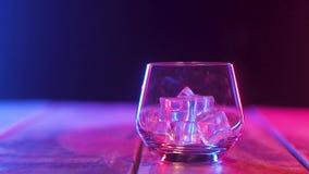 Sulla tavola è un vetro vuoto del nastro scozzese con i cubetti di ghiaccio primo piano panoramico video d archivio
