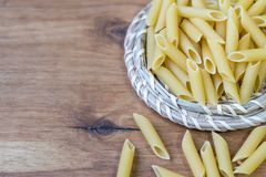 Sulla tavola, la pasta è sparsa sulla superficie di legno Fotografie Stock