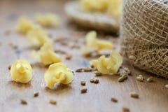Sulla tavola, la pasta è sparsa sulla superficie di legno Immagini Stock