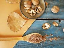 Sulla tavola, noci, seme di lino, utensili di legno, annata, cucinante alimento sano fotografia stock