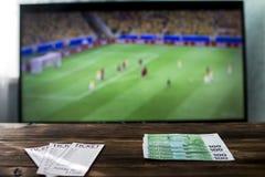 Sulla tavola, scommettere i biglietti e gli euro soldi, nei precedenti sulla TV è calcio immagine stock libera da diritti