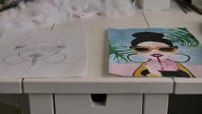 Sulla tavola sono due fogli di carta con uno schizzo e un disegno di una ragazza con i vetri che beve una bevanda con l'aiuto di  video d archivio
