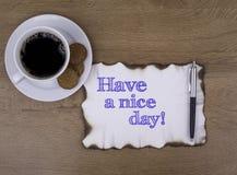 Sulla tavola un pezzo di carta e testo Abbia un giorno piacevole! fotografia stock