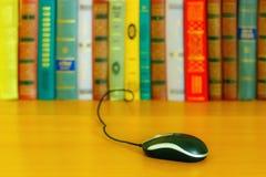 Sulla tavola una serie di libri e un topo dal computer portatile immagini stock