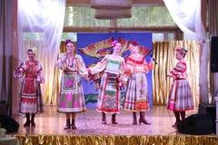 Sulle belle ragazze della fase in costumi russi nazionali, prendisole degli abiti con ricamo vibrante - gruppo di musica folk la  Fotografia Stock