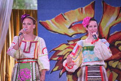 Sulle belle ragazze della fase in costumi russi nazionali, prendisole degli abiti con ricamo vibrante - gruppo di musica folk la  Fotografia Stock Libera da Diritti