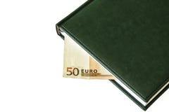 Sulle bugie di un fondo della luce un un diario e la parte di una fattura dell'euro 50 Immagini Stock Libere da Diritti