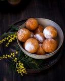Sulle guarnizioni di gomma piuma di un piatto con la polvere dello zucchero, decorata con la mimosa fiorisce Priorità bassa di le Fotografie Stock