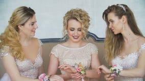 Sulle mani delle donne sono i bei braccialetti fatti dei fiori fatti a mano stock footage
