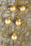 Sulle retro palle e perle di legno di natale dell'oro del fondo Immagini Stock