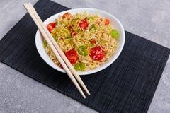 Sulle tagliatelle cinesi deliziose della tavola con le verdure ed i bastoncini fotografie stock libere da diritti