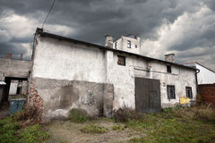Sullen abandoned warehouse with stormy sky Royalty Free Stock Photos