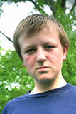 Sullen Boy. Preteen boy outdoors with sullen expression royalty free stock photography