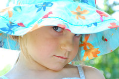 Sullen look. Little girl wearing  a blue hat looking sullenly Stock Image