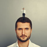 Sullen man with small man on the head Stock Photography