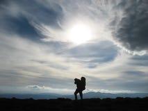 Sulouette zmęczony mężczyzny turysta przy wierzchołkiem góra obrazy stock