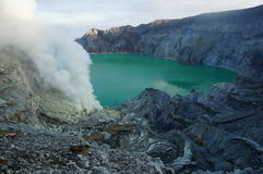 Sulphur mine, active volcano, lake. Active Java volcano - Ijen crater. Sulphur mine, Indonesia. Workers in the distance risk their lives to mine sulphur from Stock Photos