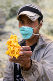 Sulphur mine man. Man works in sulphur mine holding a piece of molten sulphur that has been poured into a shape to sell to tourists, Ijen crater sulphur mine Stock Image