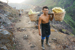 Sulphur mine strong man. Strong man carries heavy load of sulphur in baskets, walking away from sulphur mine, Ijen crater sulphur mine, Java Indonesia Stock Photography