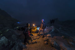 Sulphur worker talking to local guide inside Ijen crater in East Java, Indonesia Royalty Free Stock Photos