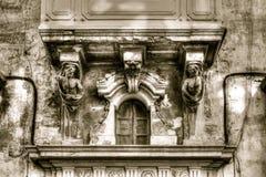 Sulptures onder een balkon, klein venster dicht blind met decor royalty-vrije stock afbeelding