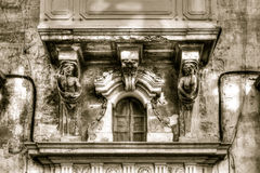 Sulptures under a balcony, small window close shutter with decor Royalty Free Stock Image