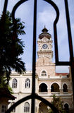 Sultan Abdul Samad Building with Clock Tower. A view of the Sultan Abdul Samad Clock Tower in Kuala Lumpur through the perimeter grille fence. This building used Stock Image