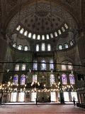 Sultan Ahmed Mosque. A popular tourist site, the Sultan Ahmed Mosque continues to function as a mosque today; men still kneel in prayer on the mosque& x27;s lush Royalty Free Stock Photography