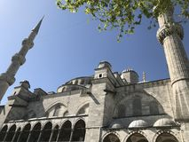 Sultan Ahmed Mosque. A popular tourist site, the Sultan Ahmed Mosque continues to function as a mosque today; men still kneel in prayer on the mosque& x27;s lush Stock Photography