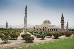 Sultan Qaboos Grand Mosque, Muscat, Oman during the afternoon in the blue sky and clouds and mountains in view stock image