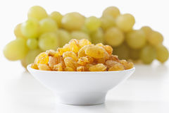 Sultana raisins and grapes on white background Royalty Free Stock Images