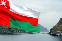 Sultanat von Oman-Staatsflagge mit Küstenlinie und traditionellem Boot nannte Dow im Hintergrund stockbilder