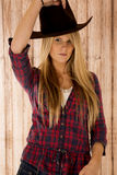 Sultry blond model wearing a cowboy hat barnwood b Royalty Free Stock Photos
