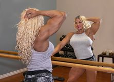 Kim Buck, Enticing Woman Bodybuilder. Sultry female professional bodybuilder Kim Buck from Georgia, pauses to pose in the gym, displaying a powerful bice and royalty free stock photo