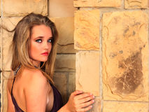 Sultry looking blonde lady next to stone wall Stock Photo