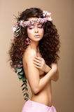 Sultry skönhet. Attraktiv naken kvinna med den långa lockiga hår och kranen av blommor Royaltyfri Bild