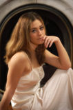 Sultry Woman. Soft focus glow portrait of beautiful woman, wearing a nightgown, sitting in front of a marble fireplace arch Stock Photography