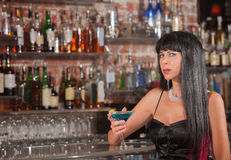 Sultry Woman with Martini. Sultry mature woman in black dress with blue martini royalty free stock photos