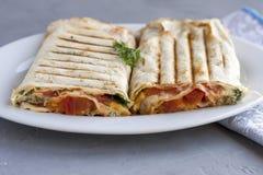 Suluguni en pain pita avec des verts et tomates d'un plat blanc photos libres de droits