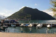 SULZANO ITALIEN - MAJ 13, 2017: hamn av den Sulzano staden med fartyg på sjön Iseo med Monte Isola på bakgrunden, Italien Royaltyfri Bild