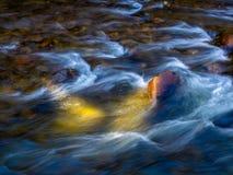 Sumário: Água que flui sobre rochas do rio imagem de stock