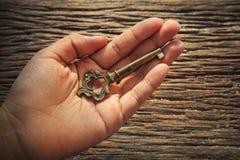 Sumário da chave do metal na mão esquerda contra textured da madeira da casca Fotos de Stock