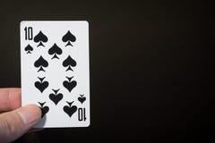 Sumário: equipe a mão que guarda pás do cartão de jogo dez em um fundo preto com copyspace fotografia de stock royalty free