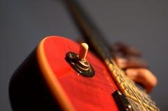 Sumário macro da guitarra elétrica, mão que joga a guitarra Fotografia de Stock Royalty Free
